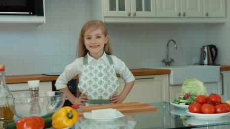 Chica-Riendo-Chef-En-La-Cocina-Mirando-A-La-Cámara-Pulgar-Arriba-Ok