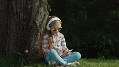 Laughing-girl-listens-to-music-from-her-phone-under-a-tree