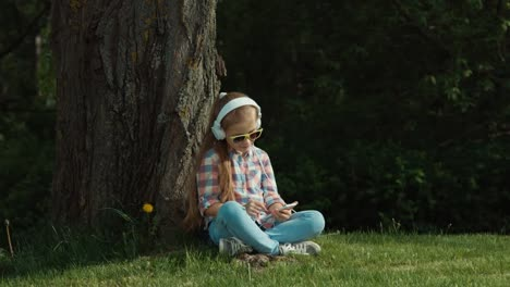 Laughing-girl-listens-to-music-from-her-phone-under-a-tree-1