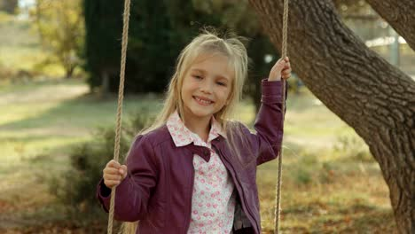 Laughing-Girl-On-A-Swing-Under-A-Tree-In-The-Park