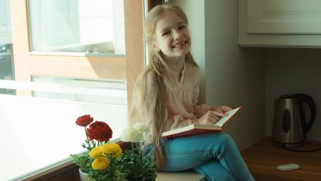 Laughing-Girl-Reading-A-Book-And-Sitting-On-The-Windowsill-She-Looks-Into-Th