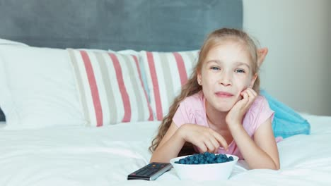 Laughing-Girl-Watching-Tv-Lying-On-The-Bed-Child-Eating-Blueberries