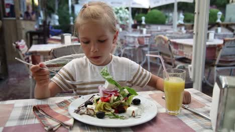 Little-Girl-Eating-A-Greek-Salad-In-The-Cafe-And-Looking-At-The-Camera