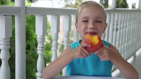 Little-Girl-Eating-A-Big-Peach-And-Smiling-At-The-Camera-Thumbs-Up