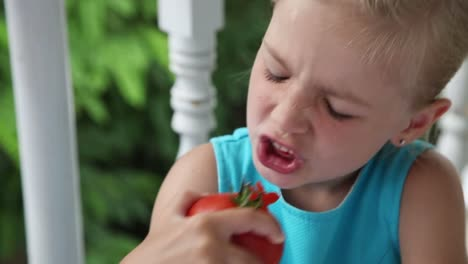 Little-Girl-Eating-A-Big-Red-Tomato-And-Smiling-At-The-Camera-Closeup-Portrait