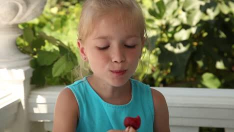 Little-Girl-Eating-Strawberry-In-The-Garden