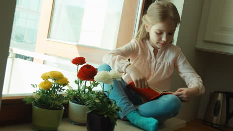 Little-Girl-Reading-A-Book-Sitting-On-The-Windowsill