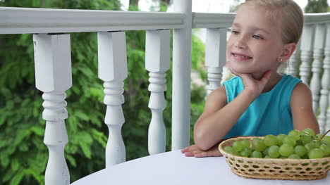 Little-Girl-Sitting-At-The-Table-And-Clapping