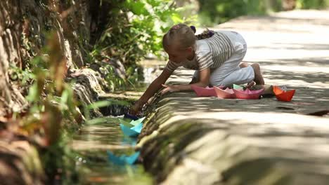 Little-Girl-Standing-On-Knees-And-Starts-The-Paper-Boats-On-Brook