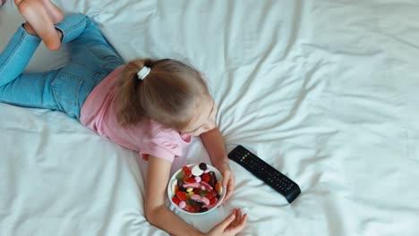 Lonely-Child-Girl-Switching-Tv-Lying-On-The-Bed-Child-Shocked-Tv-Child-Eating