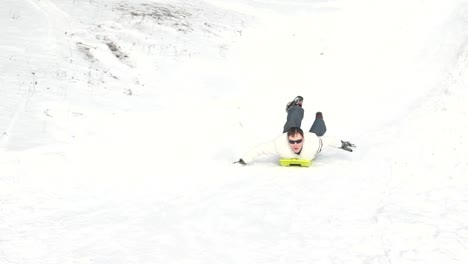 Man-Riding-On-A-Sledge-Down-Hills-He-Is-Lying-On-Toboggan
