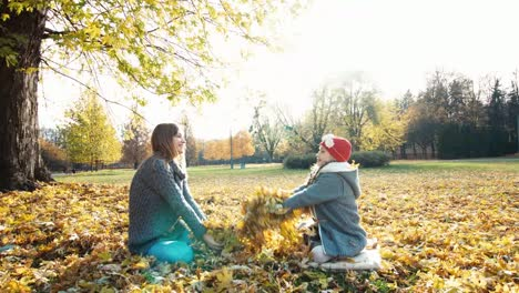 Mother-And-Daughter-Throwing-Autumn-Leaves-In-The-Park-And-Laughing