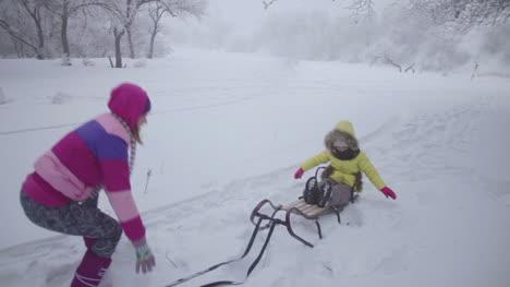 Mutter-Und-Tochter-Werfen-Schnee-Im-Winterwald