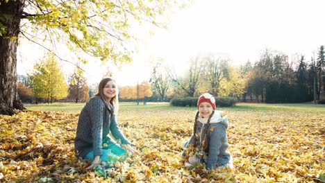 Mutter-und-Tochter-Wirft-Im-Park-Herbstlaub-Hoch-und-Lacht
