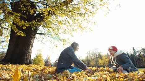 Mutter-und-Tochter-Wirft-Herbstlaub-Im-Park-Hoch