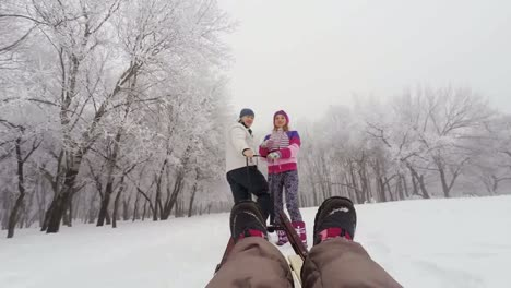 Mother-And-Father-Pulling-Sledge-With-Their-Daughter