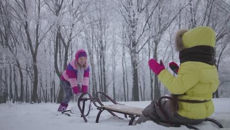 Madre-Arrojando-Nieve-A-Su-Hija-Ella-Está-Sentada-En-Un-Trineo-En-Invierno