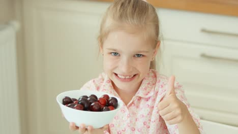 Portrait-Child-Girl-Holding-A-Bowl-Of-Cherries-And-Smiling-At-Camera