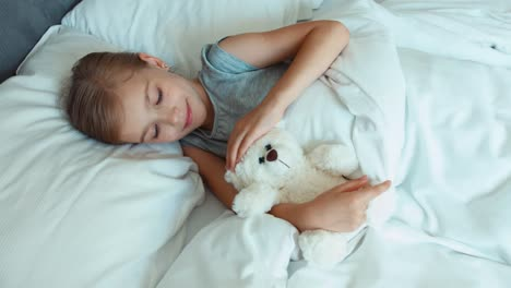Portrait-Girl-6-8-Years-Old-Sleeping-With-Teddy-Bear-In-A-Bed-And-Wakes-Up