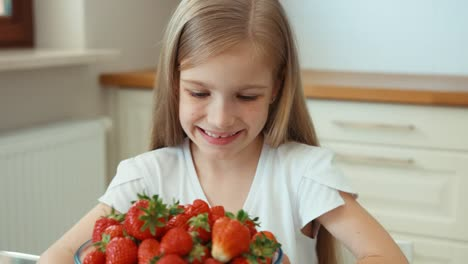 Portrait-Girl-Admiring-A-Large-Plate-Of-Strawberries-And-Looking-At-Camera