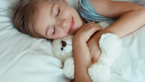 Portrait-Girl-Child-Hugging-Teddy-Bear-In-A-Bed-Top-View