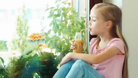 Retrato-Niña-Bebiendo-Jugo-Y-Sonriendo-A-La-Cámara