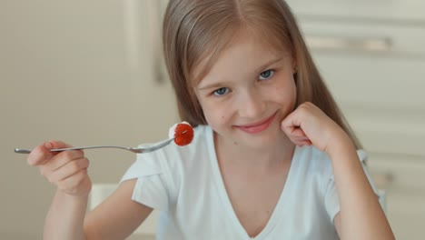 Portrait-Girl-Eating-A-Strawberry-From-A-Plate-And-Smiling-At-The-Camera