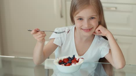 Portrait-Girl-Eating-Raspberries-From-A-Plate-And-Smiling-At-The-Camera