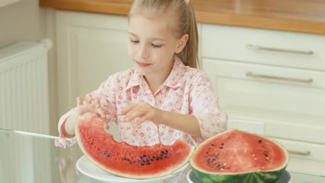 Portrait-Girl-Eating-Watermelon-In-The-Kitchen-And-Smiling-At-The-Camera