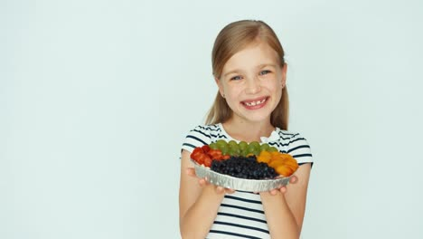 Portrait-Girl-Holding-Cake-With-Fruit-Near-Face-On-The-White-Background