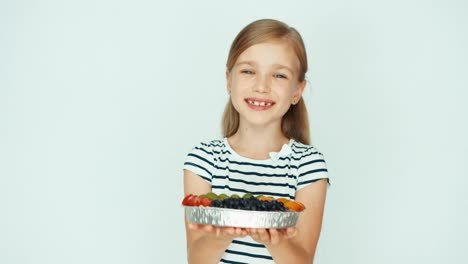 Portrait-Girl-Holding-Cake-With-Fruit-On-The-White-Background