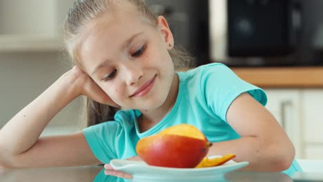 Portrait-Girl-Looking-At-Mango-And-Camera-Child-Promotes-Fruit-Mango