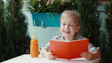Portrait-Girl-Reading-A-Book-And-Smiling-At-Camera-Thumb-Up-Ok