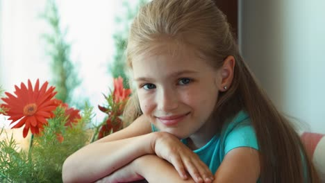 Portrait-Girl-Sitting-On-The-Windowsill-Against-The-Window-And-Looking-In-Window