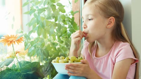 Portrait-Girl-Sniffing-And-Eating-Gooseberries