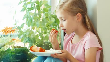 Portrait-Girl-Sniffing-Tomato-Against-Window-And-Smiling