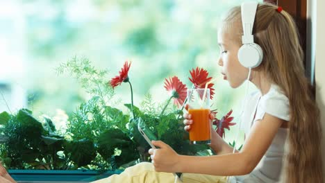Portrait-Girl-Using-Tablet-PC-And-Drinking-Juice-Against-The-Flower