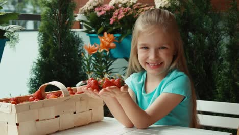 Portrait-Girl-With-Handful-Of-Strawberries-Child-Looking-At-Camera-And-Smiling