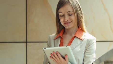 Portrait-Happy-Businesswoman-Using-Tablet-PC-And-Smiling-At-Camera