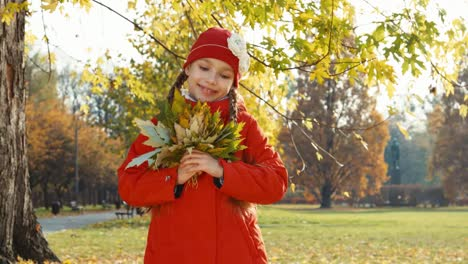 Portrait-Happy-Child-Girl-Holding-A-Bouquet-Of-Autumn-Leaves-In-The-Park-And
