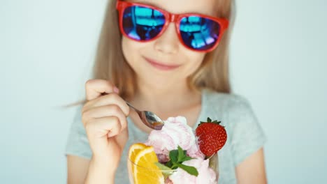 Portrait-Happy-Child-In-Sunglasses-Eating-Ice-Cream-And-Smiling-At-The-Camera
