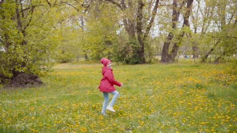 7-8-Years-Girl-In-Red-Jacket-And-Hat-Running-In-The-Park-In-The-Spring