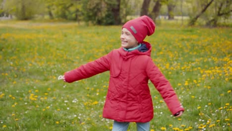 7-8-Years-Girl-In-Red-Jacket-And-Hat-Spinning-In-The-Park-In-The-Spring