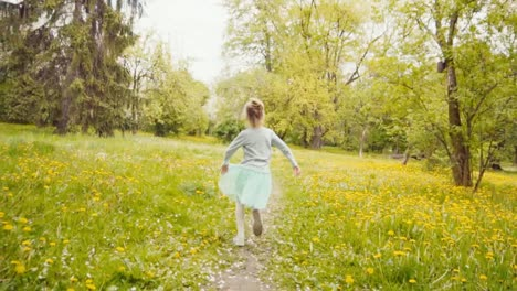 7-8-Years-Old-Girl-In-Blue-Skirt-Spinning-And-Running-In-The-Park