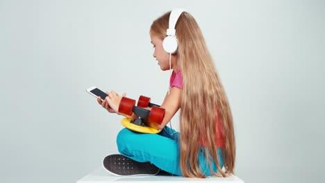 7-8-Years-School-Girl-Listening-Música-In-Headphones-Using-Her-Cell-Teléfono