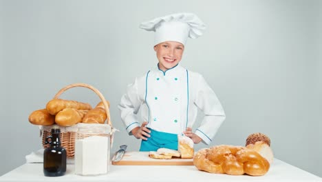 Baker-Girl-Standing-Near-Kitchen-Table-With-Bakery-Products-And-Smiling