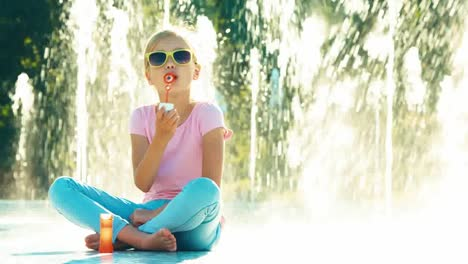 Beautiful-Shot-Of-Girl-Blowing-Soap-Bubbles-Near-Fountain-And-Laughing