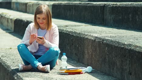 Beautiful-Student-Using-Your-Cell-Phone-And-Smiling-At-Camera