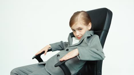 Business-Girl-7-8-Years-Old-In-A-Business-Suit-On-White-Background-Sitting