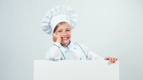 Chef-7-8-Years-Behind-The-Whiteboard-Waving-Hand-And-Looking-At-Camera